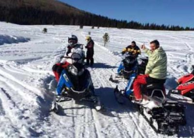 group of sledders on snowmobiles